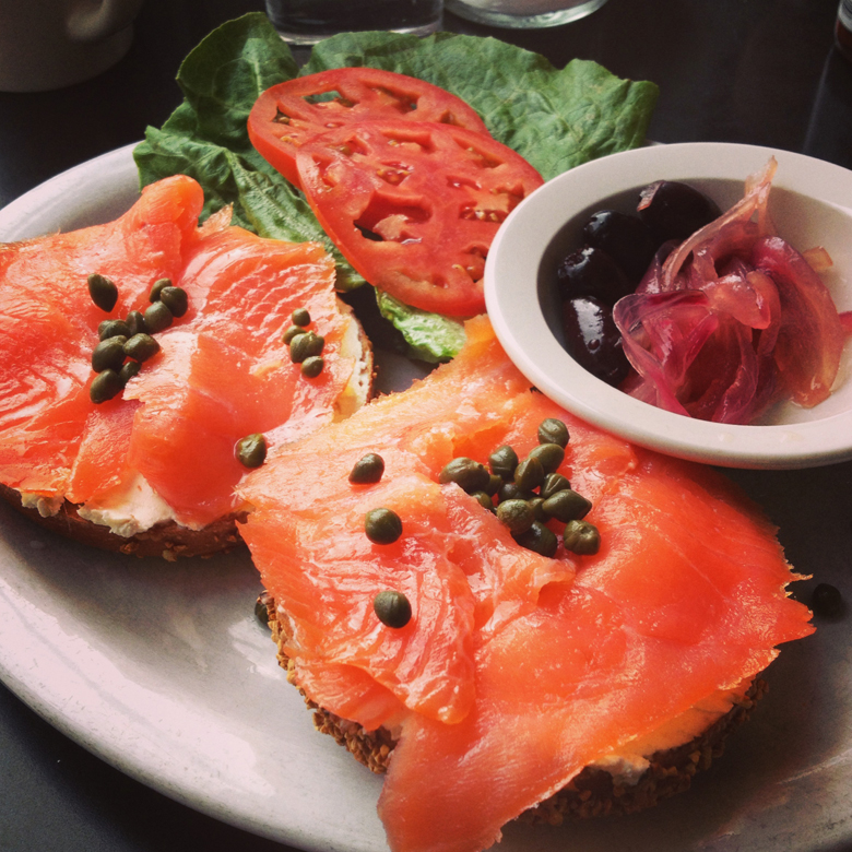 Smoked salmon on bagel with pickles and salad at Kenny and Zuke's